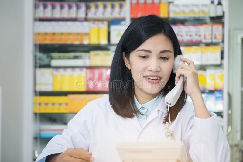 Apteka pracownik opowiada telefonem, Atrakcyjna młoda uśmiechnięta kobieta przy biurkiem z telefonem ucho zdjęcia stock