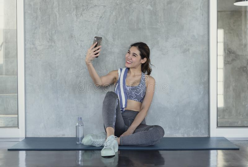 Aptidão ativa de sorriso atrativa do asiático novo que senta-se no assoalho do gym e que toma um selfie fotografia de stock
