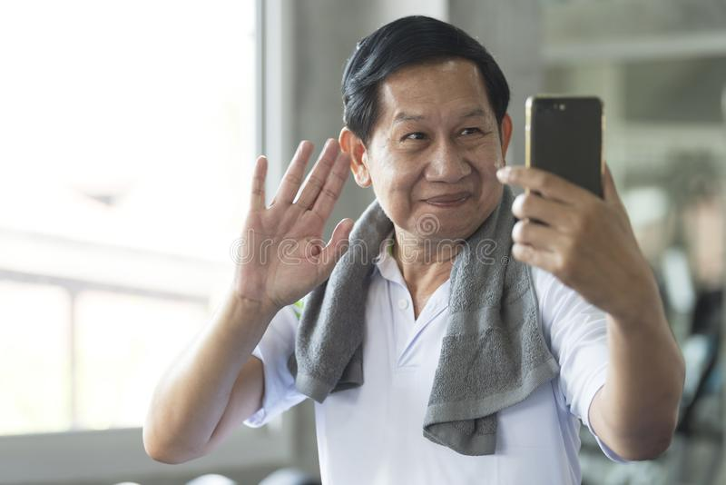 Aptidão ativa de sorriso atrativa do homem asiático superior no gym e em tomar um selfie foto de stock royalty free