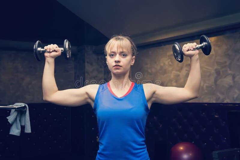 Aptidão Conceito do esporte workout A menina loura guarda pesos pretos Menina da aptidão Estilo de vida saudável Treinamento work fotos de stock