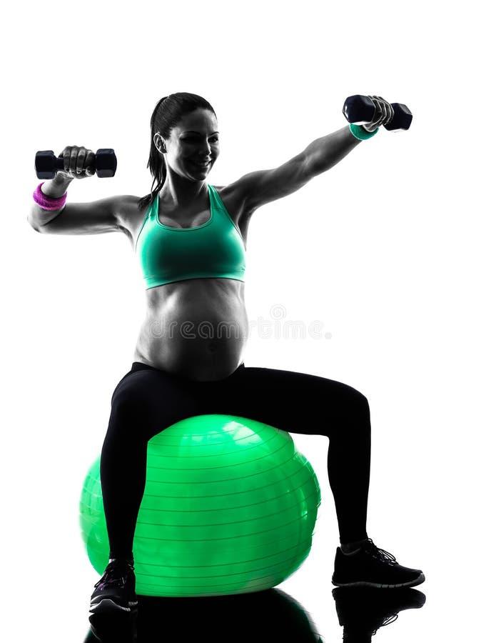 A aptidão da mulher gravida exercita a silhueta fotos de stock