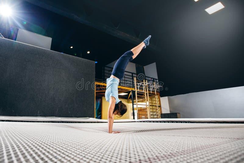 Aptidão do desportista da jovem mulher que salta no trampolim do clube foto de stock
