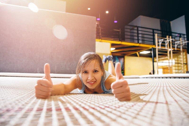 Aptidão do desportista da jovem mulher que salta no trampolim do clube fotos de stock