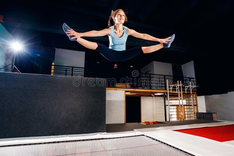 Aptidão do desportista da jovem mulher que salta no trampolim do clube fotografia de stock
