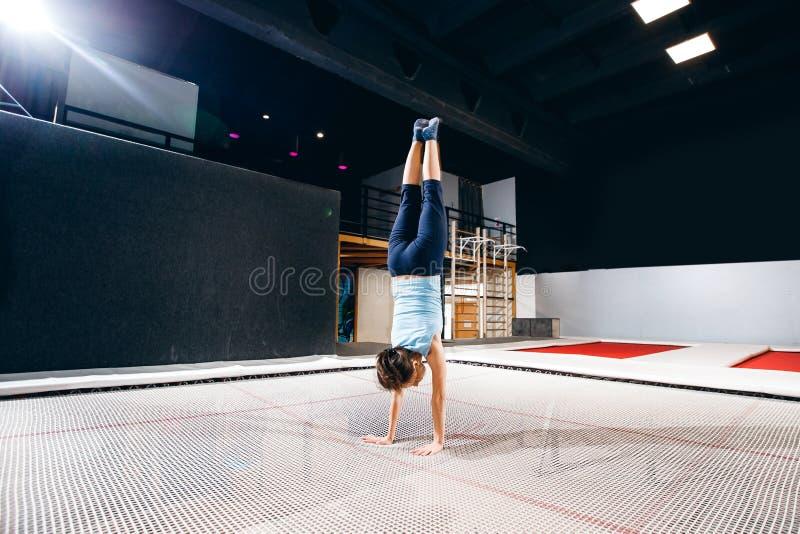 Aptidão do desportista da jovem mulher que salta no trampolim do clube foto de stock royalty free