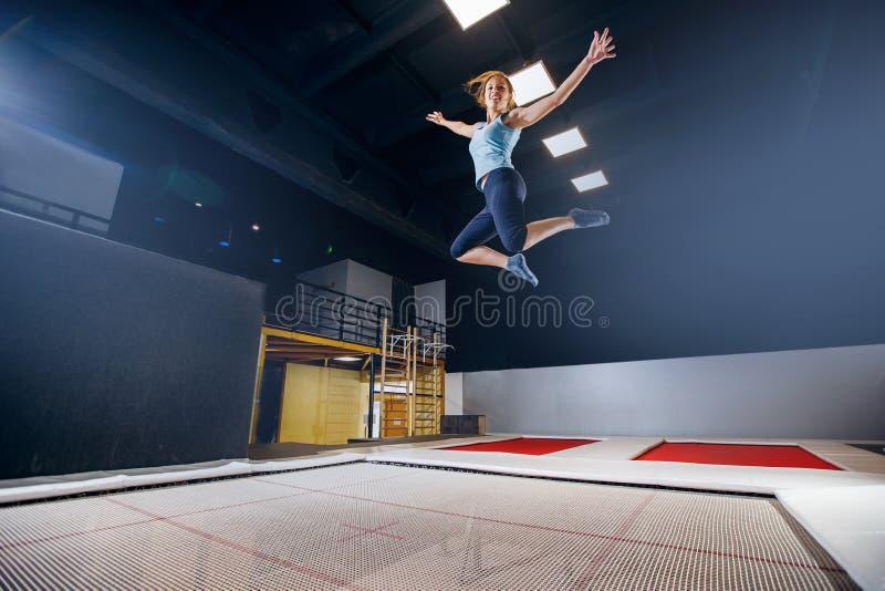 Aptidão do desportista da jovem mulher que salta no trampolim do clube imagem de stock