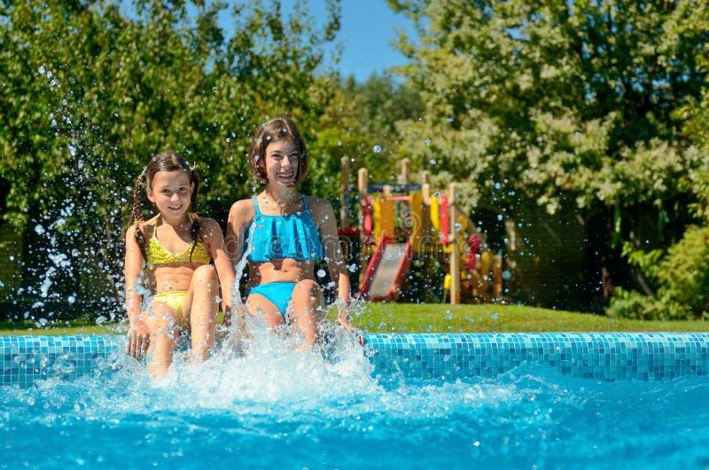 A aptidão do verão, crianças na piscina tem o divertimento, respingo de sorriso das meninas na água foto de stock royalty free