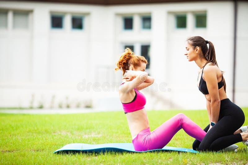 Aptidão Duas meninas consideravelmente desportivas que fazem esticando os exersises exteriores foto de stock