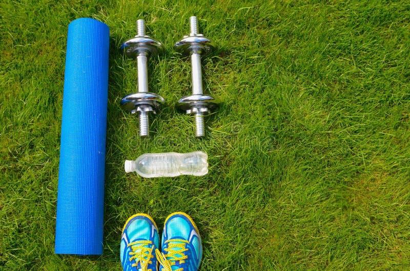 Aptidão e conceito saudável do estilo de vida, sapatas do esporte, pesos, garrafa da água e esteira na grama foto de stock royalty free