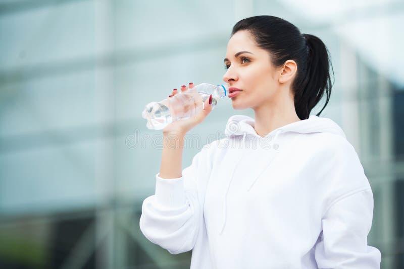 Aptidão Esporte e conceito saudável do estilo de vida - água potável da mulher após o exercício no parque imagens de stock