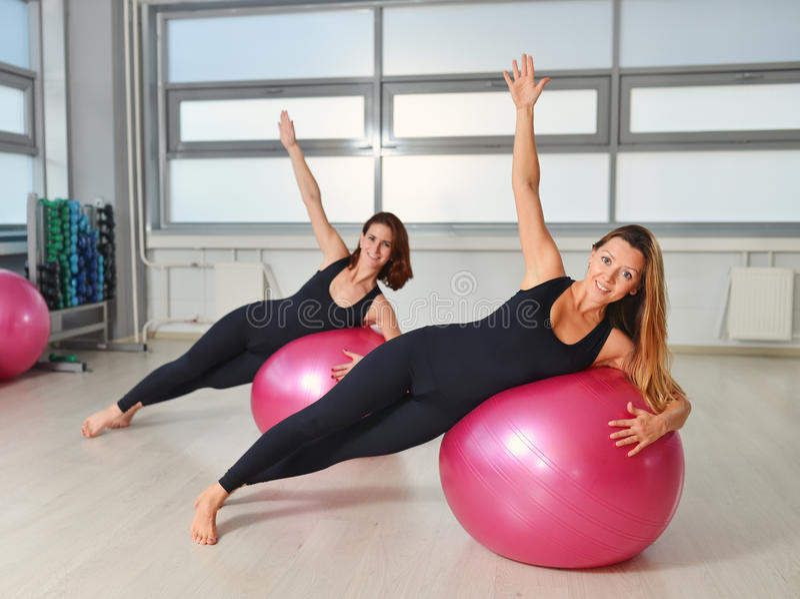 Aptidão, esporte, exercitando o estilo de vida - grupo de mulheres que fazem exercícios com bolas do ajuste em uma classe de Pila foto de stock royalty free