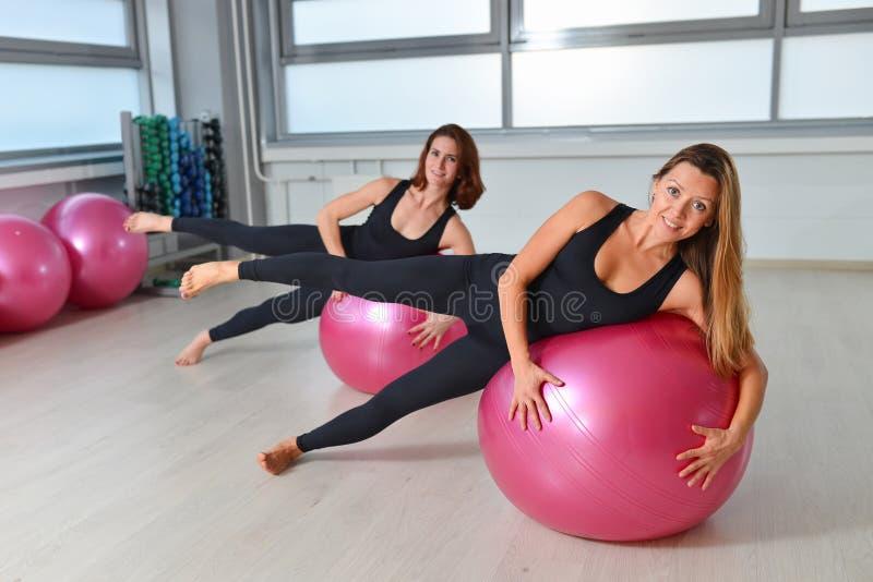 Aptidão, esporte, exercitando o estilo de vida - grupo de mulheres que fazem exercícios com bolas do ajuste em uma classe de Pila imagens de stock
