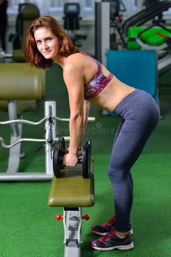 Aptidão, esporte, exercitando o estilo de vida - menina com os pesos que fazem exercícios no gym, mulher desportiva que olha a câ imagem de stock