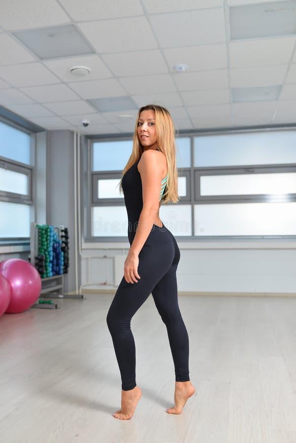 Aptidão, esporte, exercitando o estilo de vida - mulher no bodysuit preto que levanta no gym imagens de stock