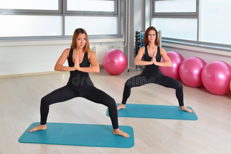 Aptidão, esporte, exercitando o estilo de vida - o grupo fêmea que faz alguma ioga exercita no gym fotografia de stock
