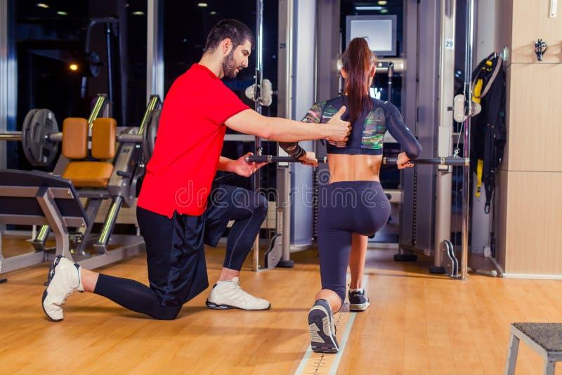 Aptidão, esporte, treinamento e conceito dos povos - mulher de ajuda do instrutor pessoal que trabalha com no gym imagem de stock royalty free