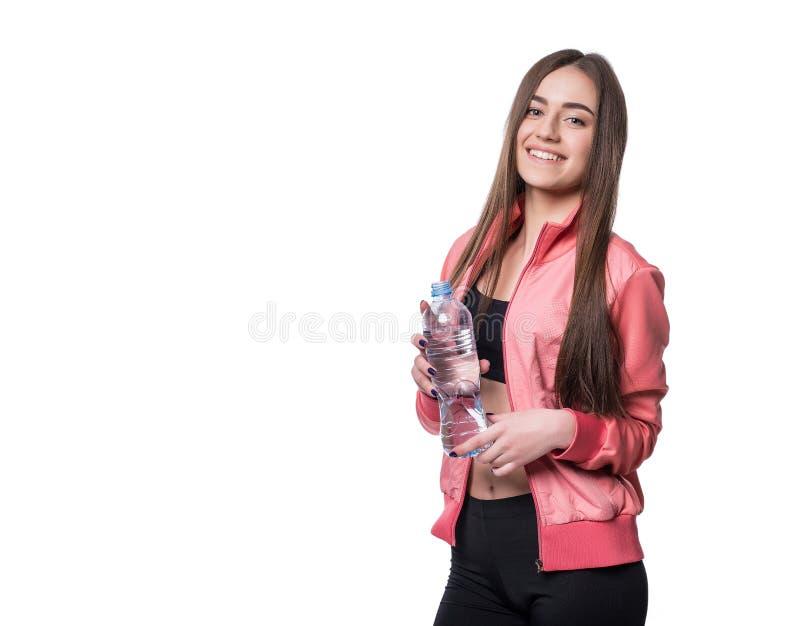 Aptidão-menina de sorriso nova no sportswear com a garrafa da água pura isolada no fundo branco Conceito saudável do estilo de vi foto de stock