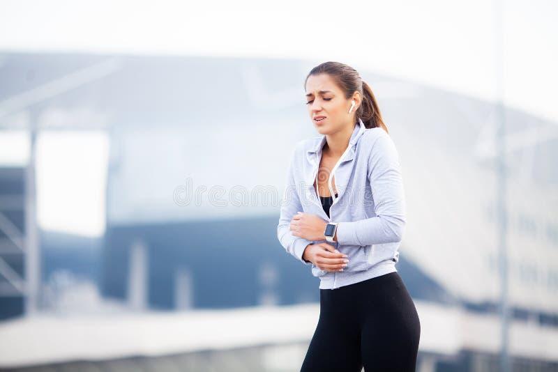Aptidão A mulher tiver ferimento do acidente e fê-lo-ir nos braços quando exercício em exterior, conceito da dor de músculo foto de stock royalty free