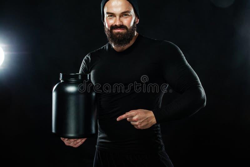 A aptidão nova muscular feliz e saudável ostenta o homem com um frasco da nutrição dos esportes - proteína, gainer e caseína fotografia de stock royalty free