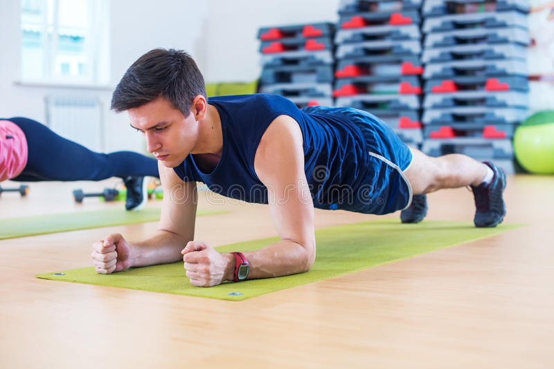 Aptidão que treina o homem desportivo atlético que fazem o exercício da prancha no gym ou a classe da ioga que exercita o exercíc foto de stock