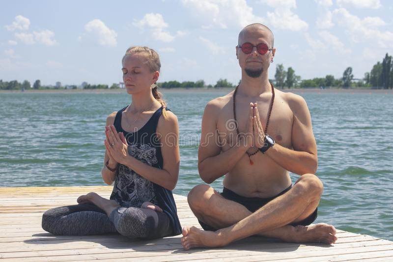 Aptid?o, esporte, ioga e conceito saud?vel do estilo de vida - grupo de pessoas que medita na pose dos l?tus no beliche do rio ou imagem de stock royalty free