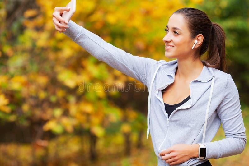 Aptid?o Mulher do esporte que toma a foto do selfie no telefone celular no parque do ver?o fotos de stock royalty free