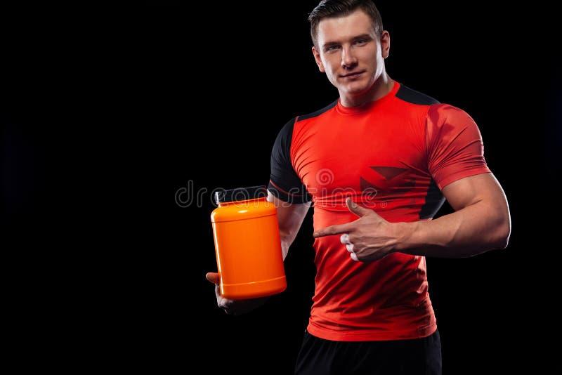 A aptid?o nova muscular feliz e saud?vel ostenta o homem com um frasco da nutri??o dos esportes - prote?na, gainer e case?na frau imagens de stock royalty free