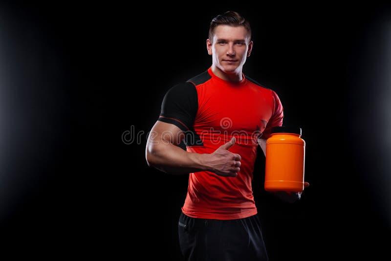 A aptid?o nova muscular feliz e saud?vel ostenta o homem com um frasco da nutri??o dos esportes - prote?na, gainer e case?na imagens de stock