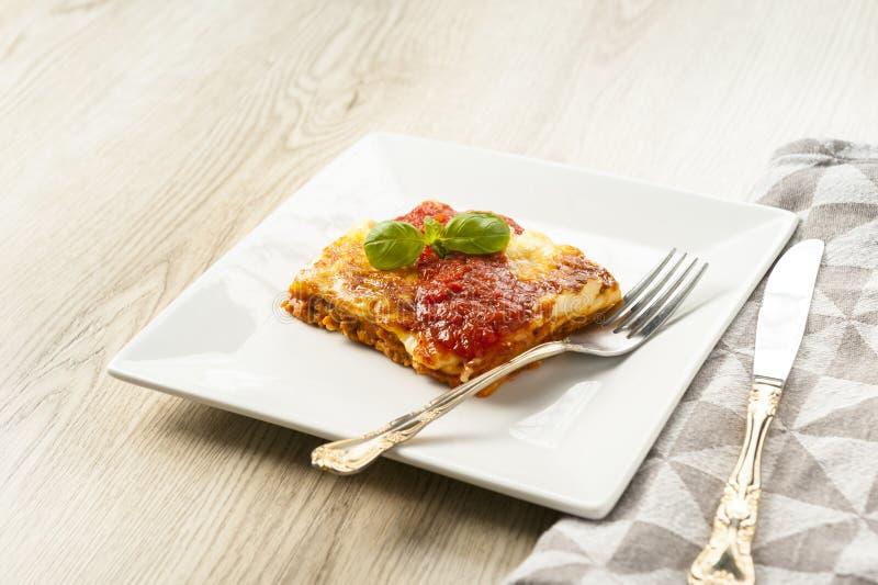 Aptitretande del av lasagner på en vit platta med tomatsås arkivbild