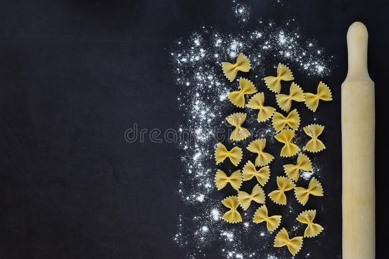 Aptitretande pasta med dina egna händer - många fjärilar på en mörk bakgrund och kavel royaltyfri bild