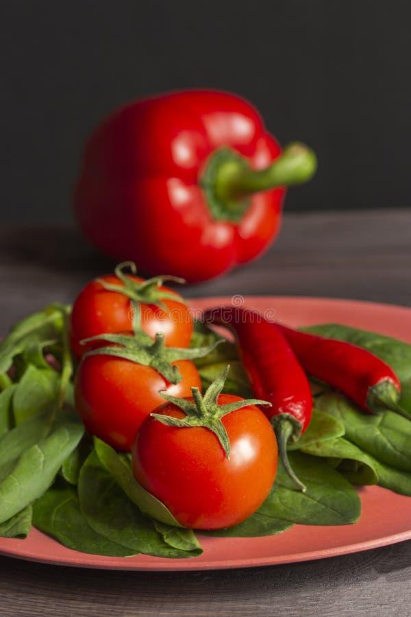 Aptitretande röda grönsaker tre tomater med sidor, glödheta chilipeppar, paprika och gröna spenatsidor på en röd bambu fotografering för bildbyråer