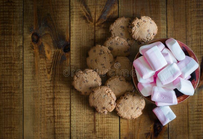 Aptitretande rosa och vita marshmallower på en platta, choklade kakor på måfå spridda på en trätabell arkivfoton