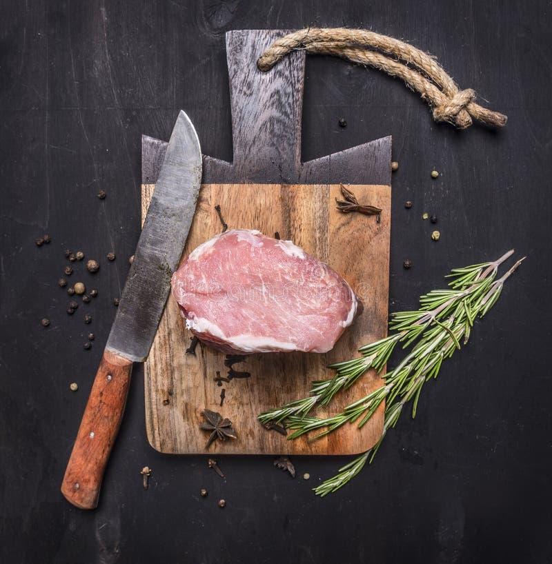 Aptitretande stycke av rå grisköttbiff på tappningskärbräda med örter och kryddor för kött med en kniv på trälantlig backgroun arkivfoton