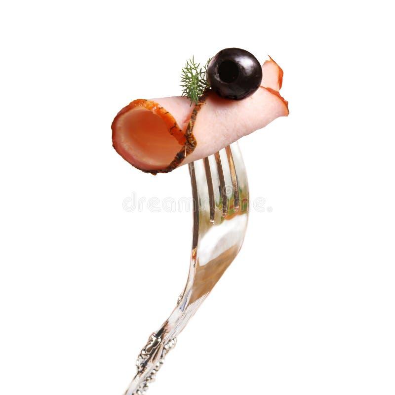 Aptitretande stycke av r?kt k?tt med oliv och en kvist av dill som kl?mmas fast p? en gaffel royaltyfri foto