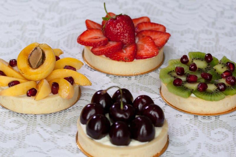Aptitretande tartlets med olika berrys och frukter ligger på en vit bordduk royaltyfria bilder