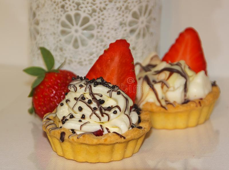 Aptitretande tartlets med piskade kräm och jordgubbar Kräm, arkivfoton