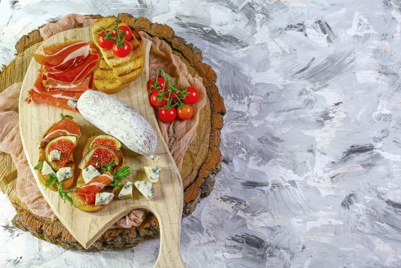 Aptitretare bordlägger med italienska antipastimellanmål Brushetta eller autentiska traditionella spanska tapas ställde in, ostva arkivbild