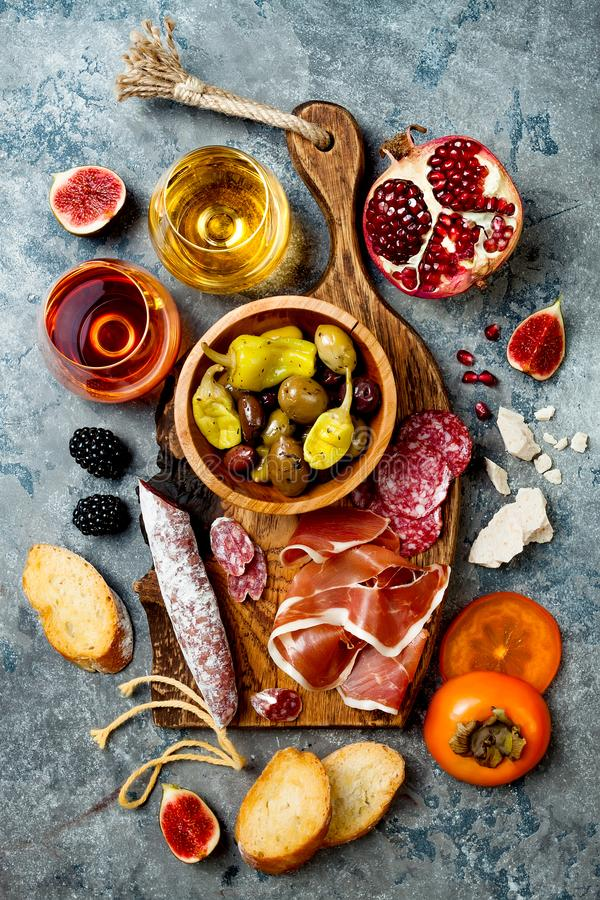 Aptitretare bordlägger med italienska antipastimellanmål och vin i exponeringsglas Charkuteribräde över grå färgbetongbakgrund royaltyfri bild