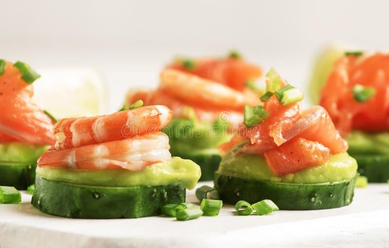 Aptitretare med gurkan, avokadot, den salta forellen och räka på vit köktabebakgrund, festligt mellanmålbegrepp, selektiv fokus arkivbild
