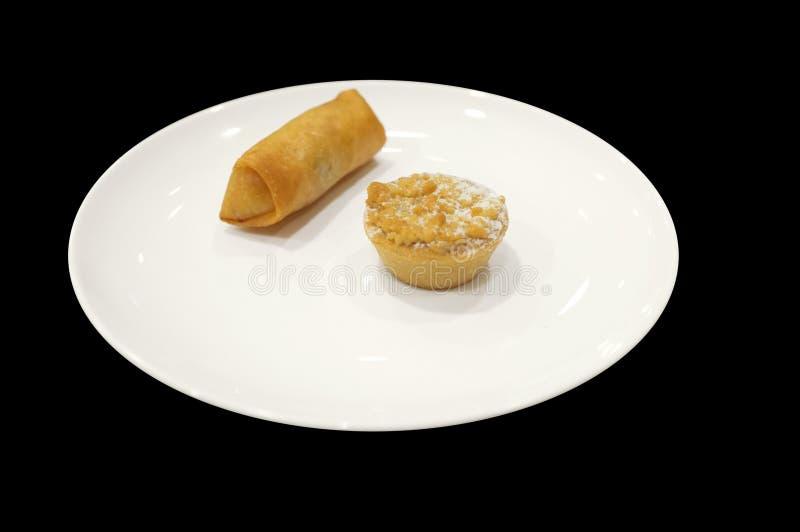 Aptitretaremärkduk med vårrulle och syrligt på den vita maträtten royaltyfri foto