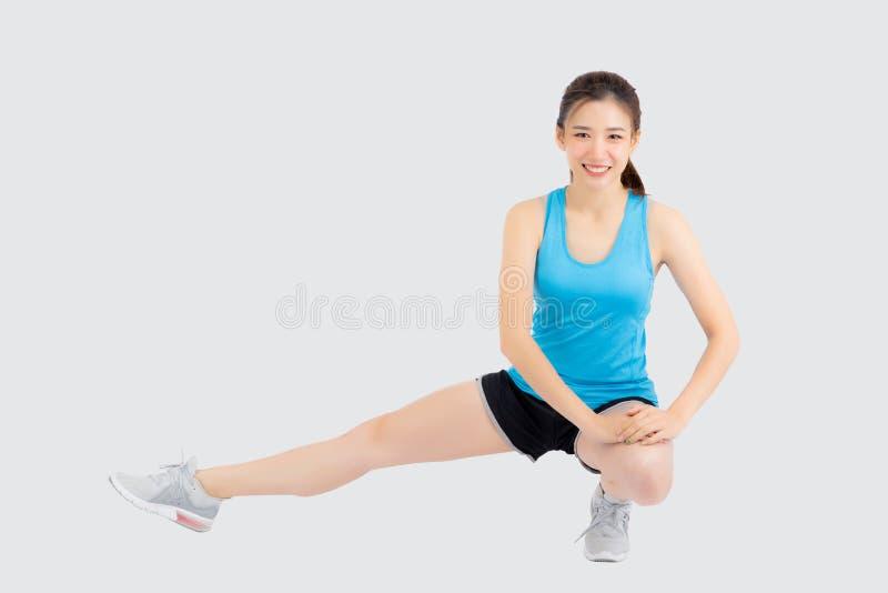Aptitud asiática joven de la mujer del retrato hermoso con estirar la pierna aislada en el fondo blanco imagenes de archivo