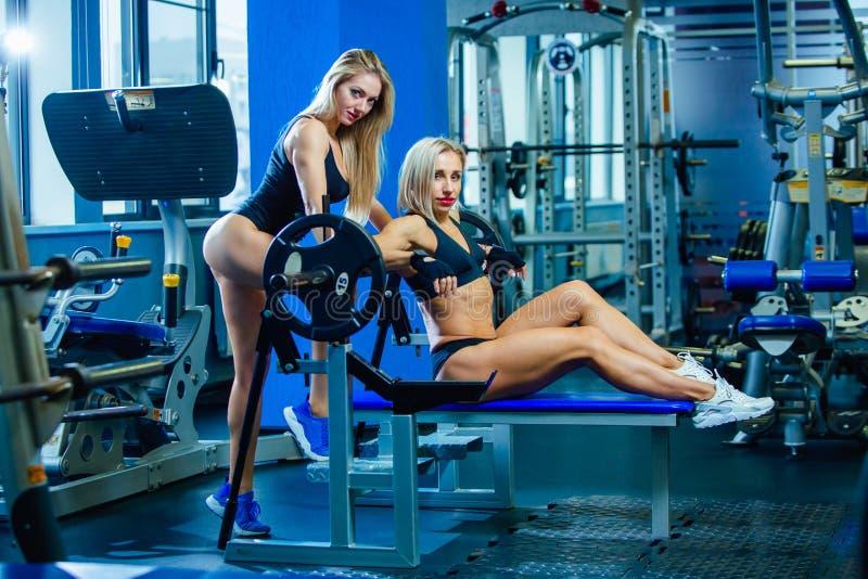 Aptitud brutal dos amigos femeninos con un muscular en el gimnasio Deportes y aptitud - concepto de forma de vida sana Aptitud foto de archivo libre de regalías