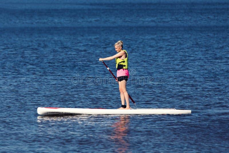 Aptitud del SORBO - mujer en el tablero de paleta en el lago imagen de archivo