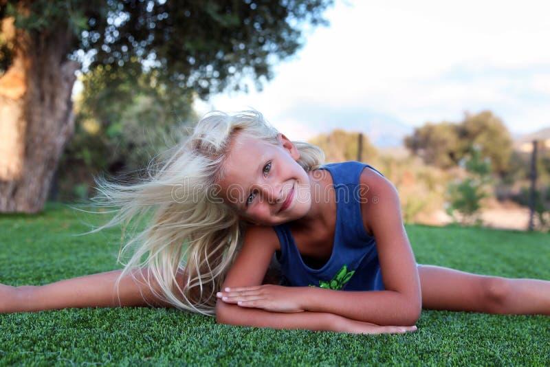 Aptitud, deporte, ejercicio, el estirar y concepto de la gente - muchacha rubia sonriente que hace fracturas en la hierba fotografía de archivo libre de regalías