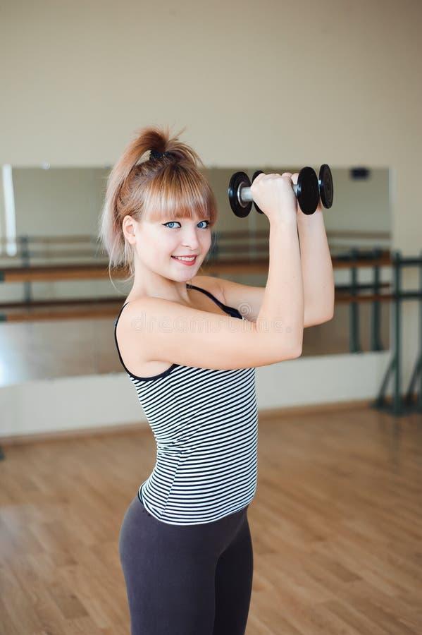 Aptitud, deporte, ejercitando forma de vida - la mujer joven atractiva que hace el levantamiento de pesas ejercita en el gimnasio foto de archivo