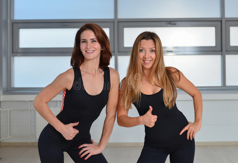 Aptitud, deporte, ejercitando la forma de vida - dos mujeres jovenes felices que se unen cercanas en un gimnasio y que muestran l fotografía de archivo