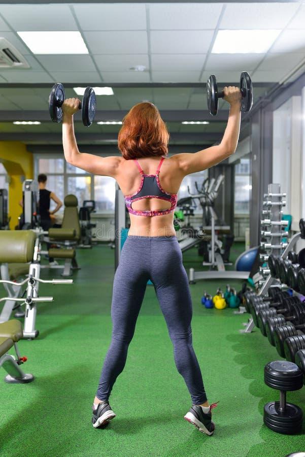 Aptitud, deporte, ejercitando la forma de vida - mujer con las pesas de gimnasia que hacen ejercicios en gimnasio imagenes de archivo