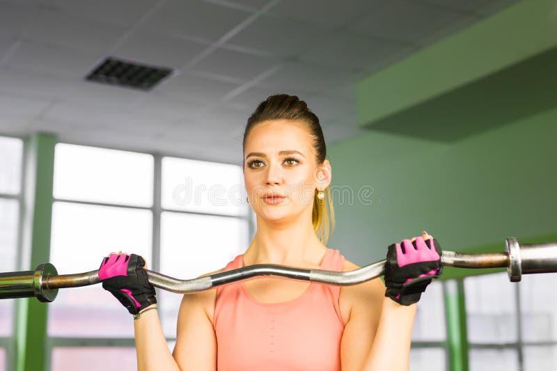 Aptitud, deporte, el powerlifting y concepto de la gente - mujer deportiva que ejercita con el barbell en gimnasio foto de archivo libre de regalías