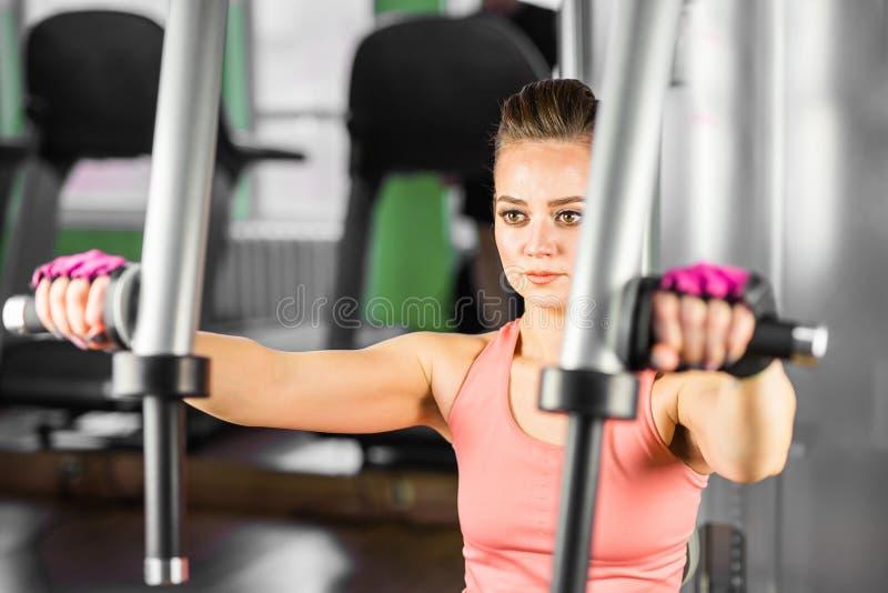 Aptitud, deporte, el powerlifting y concepto de la gente - mujer deportiva que hace entrenamiento en gimnasio fotos de archivo libres de regalías