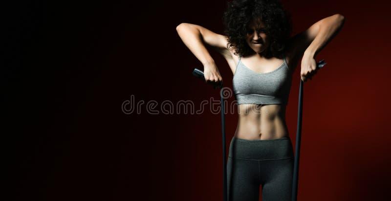 Aptitud, deporte, entrenamiento, gente y concepto de la forma de vida - mujer que hace ejercicios con el ampliador o la banda de  imagen de archivo